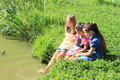 Three girls washing their feet young in dresses in water Stock Photos