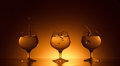 Three glass cognac splashes beverage dark gold background Stock Images