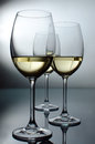 Three glasses backlight wine on a glass table Stock Photo