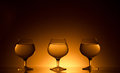 Three glasses beverage gold dark background Stock Images