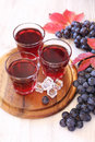 Three glasses of grape juice with ice and black grapes