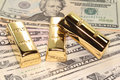 Three gold bars on dollar bills Royalty Free Stock Photo