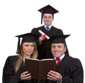 Three graduates together in a triangle isolated on white two reading book and one with scroll Royalty Free Stock Photos