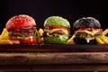 three, hamburgers on colorful bred buns Royalty Free Stock Photo