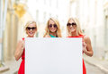 Three happy blonde women with blank white board summer holidays travel tourism and advertisement concept in the city Stock Photography