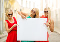 Three happy blonde women with blank white board summer holidays travel tourism and advertisement concept in the city Royalty Free Stock Image