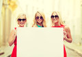 Three happy blonde women with blank white board Royalty Free Stock Photo