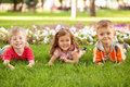 Three happy children lying on the grass two boys and a girl lawn Royalty Free Stock Photo