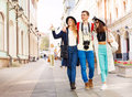 Three happy friends hugging in row and walking hug walk during sightseeing on the european street during summer day time Stock Photos