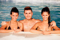 Three happy friends in the pool with a blue water of background Royalty Free Stock Image