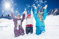 Three happy girls having fun with snow years old throwing in the air at once Stock Images
