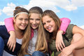 Three happy girls hug at background of sky Royalty Free Stock Image