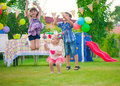 Three happy kids dancing during birthday party Stock Photos