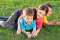 Three happy kids playing on the meadow group of green Royalty Free Stock Photo
