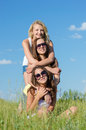 Three happy pretty girls embracing against blue sky teen sitting on green grass and on bright summer day Royalty Free Stock Photo