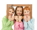 Three happy smiling kids looking picture frame Stock Photos