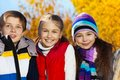 Three happy smiling teen kids close portrait of boy and two girls in autumn clothes on sunny day with faces wearing warm clothes Royalty Free Stock Photos