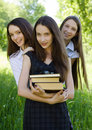 Three happy student girl with books in the park Stock Photos