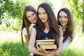 Three happy student girl with books in the park Royalty Free Stock Photography