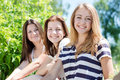 Three happy teen girl friends looking together in one direction on bright summer day Royalty Free Stock Images
