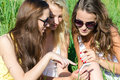 Three happy teen girl friends and mobile phone looking on while sitting on green lawn on summer day Stock Photo