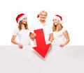 Three happy teenagers in christmas hats pointing on a banner large blank with red arrow the image is isolated white Stock Photography