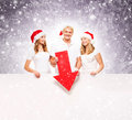 Three happy teenagers in christmas hats pointing on a banner large blank with red arrow the image is taken purple Stock Images