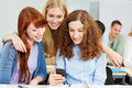 Three happy women checking social media smartphone university Royalty Free Stock Photos