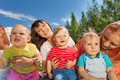 Three happy women holding cute toddlers in park sitting together during wonderful summer day Stock Photos