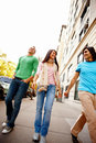 Three happy young friends walking together Stock Photo