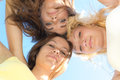 Three happy young woman friends looking down against blue sky teen girls background Royalty Free Stock Photo
