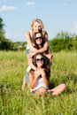 Three happy young women girl friends embracing against blue sky teen girls sitting on green grass and on bright summer day Royalty Free Stock Image