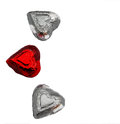 Three hearts the candy wrapped in pretty shiny foil depict symmetry color and tradition in observance of valentine s day Stock Images