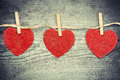 Three hearts hanging on a wooden boards background Royalty Free Stock Photos