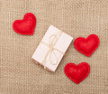 Three hearts and pink gift box stitched on sackcloth Royalty Free Stock Photos