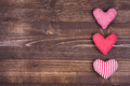 Three hearts on wood background a polka dotted one checkered one and a striped one a dark Stock Photography