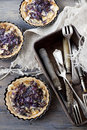 Three homemade purple cabbage and cheese rustic quiche and vintage box with silverware Royalty Free Stock Photo