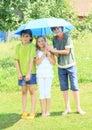Three kids with blue umbrella Royalty Free Stock Photo