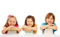 Three kids boy girls laying pile books table smiling laughing isolated white Royalty Free Stock Photo