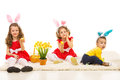 Three kids with bunny ears and easter basket sitting on the carpet home Stock Photo
