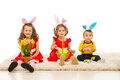 Three kids with bunny ears in a row holding easter basket and flowers and sitting on carpet Royalty Free Stock Photo