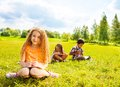 Three kids drawing in the park nice little girl sitting on grass with her friends and images outside on summer day Stock Photos