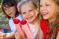 Three kids eating ice cream portrait of enjoying pops outdoors Royalty Free Stock Images