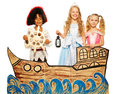 Three kids pirate and princess on cardboard ship theatrical play boy in costume of girls in dress sail studio shoot isolated white Stock Photos