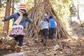 Three kids play outside shelter made of branches in a forest