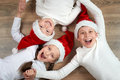 stock image of  Three kids in Santa hats lying on wooden background, having fun and happy emotions, winter holiday concept