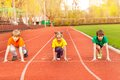 Three kids stand with bended knee ready to run Royalty Free Stock Photo