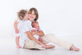 Three kids on white background with white clothes a teenage boy his cute toddler sister and a newborn brother Stock Image