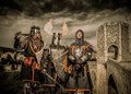 Three knight in armor against romanesque bridge over river besalu Stock Photos