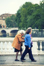 Three ladies strolling with elderly outdoor elder care women in the street on a bridge in the center of the city of rome Stock Image